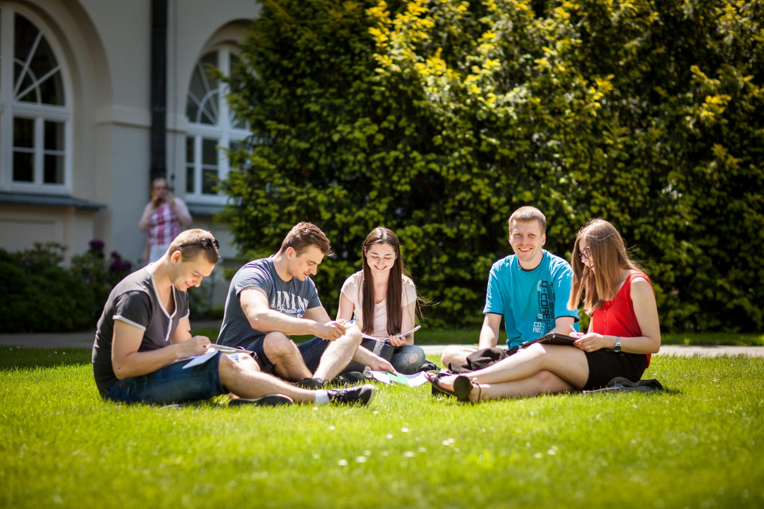 Zdjęcie przedstawiające piątkę uśmiechniętych i siedzących na trawie studentów na dziedzincu KUL