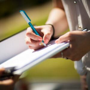 zdjęcie przedstawia dłoń trzymającą długopis i piszącą po zeszycie