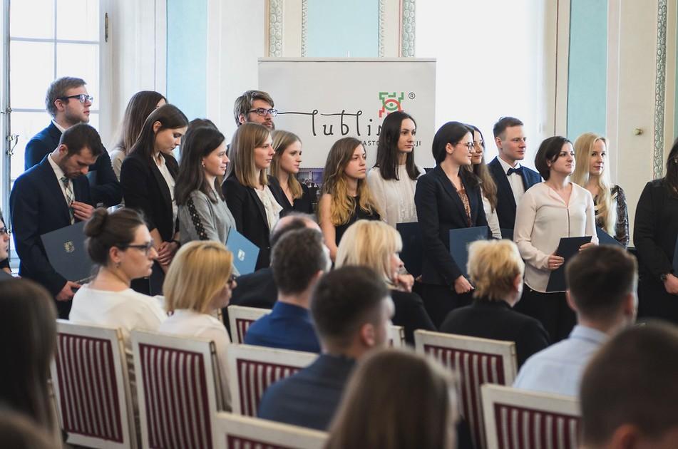 Na zdjęciu młodzi ludzie odświętnie ubrani na tle rollupu Miasta Lublin